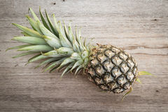 Pine apple on wooden background. Royalty Free Stock Photos