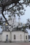 Pine branch with dark green needles closes the church building from above. Domes of Orthodox Foros Church are covered with white f. Og. Romantic picture of stock image