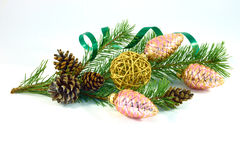 Pine branch with pine cones and Christmas decorations. Large pine cones and Christmas tree yellow straw ball with pink shiny glass fir-tree shaped cones and Stock Photography