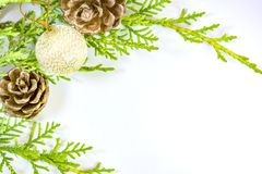 Pine branch, pinecones and shiny gold ornament on white Stock Photo