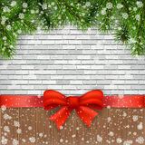 Pine branches and bow on a background of bricks. Christmas greeting card. Pine branches and bow on a background of bricks and wooden planks Stock Image