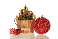 Pine branches decorated with beads in wooden bucket next to big Christmas ball and small boxes with gifts, isolated on Stock Photos