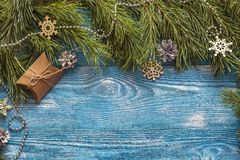 Pine branches and gift box on blue wooden background. Holidays b Stock Image