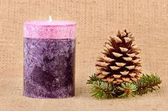 Pine cone and candle on sackcloth background Royalty Free Stock Photo