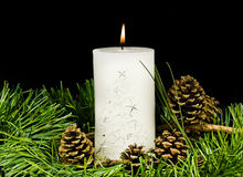 Pine cone and christmas greens and burning candle Royalty Free Stock Photos