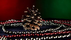 Pine cone for Christmas or New Year and beads. Christmas tree pine cone toy for Christmas tree for decoration Christmas or New Year and red and white beads stock video footage