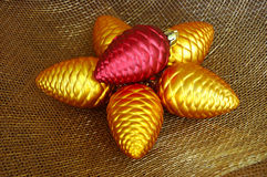 Pine Cone Christmas Ornaments. Gold and red pine cone shaped ornaments on gold holiday netting fabric royalty free stock photo