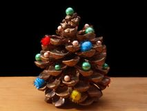 Pine cone with decorations. On a dark background and a wooden surface close-up Royalty Free Stock Photo