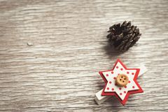 Christmas greeting card background. Pine cone  and red star  on traditional white wood background Stock Images
