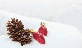 Pine Cone and Merry Red Christmas Light Bulbs Nestled in Snowy Bank. A pine cone and two red Christmas light bulbs are nestled in a snowy bank Stock Image