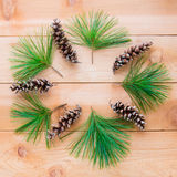 Pine cones and branches in form of Christmas wreath on  wooden t Stock Photography