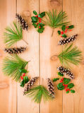 Pine cones and branches with holly berry in circle frame  on  wo Royalty Free Stock Photography