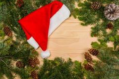 Pine cones and branches with Santa Claus red hat. On wooden background royalty free stock image