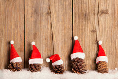 Pine cones with Christmas hats on wooden background Royalty Free Stock Photography