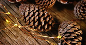 Pine cones with christmas lights on wooden plank stock footage