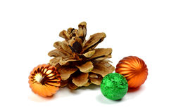 Pine cones and colored spheres. / Isolated on white /. Big beautiful cedar cones and small multi-colored spheres: the decor to create a festive mood. Children Stock Photography