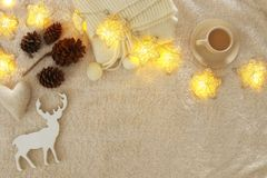 Pine cones and cup of cappuccino over cozy and fur carpet. Top view. Royalty Free Stock Images