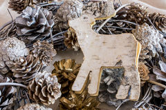 Pine cones decoration with wooden carved reindeer Stock Image