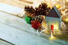 Pine cones and decorative wooden house next to gold garland lights on wooden background. copy space Stock Photos