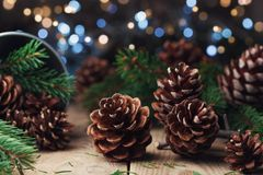 Pine cones and fir tree branch on rustic wooden table. Christmas greeting card. Royalty Free Stock Images