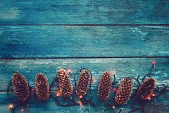 Pine cones and garland. On a blue wooden background Royalty Free Stock Photography