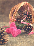 Pine cones and handmade crochet hearts in basket Stock Photography