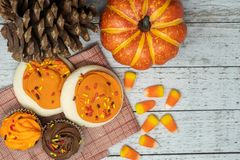 Top view of fall food arrangement with candy corn, sugar cookies and autumn cupcakes royalty free stock photos