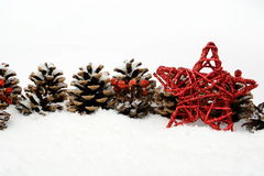 Pine cones with red star on snow in line on white Royalty Free Stock Images