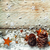 Pine cones, stars and snow in an Xmas background. Pine cones, golden orange stars and snow in an Xmas background with snow flake decorations on textured old royalty free stock image