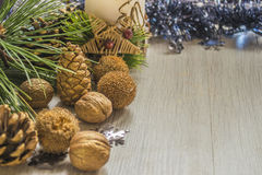 Pine cones with walnuts and candle. With christmas decoration on wooden table. Copyspace background royalty free stock photo