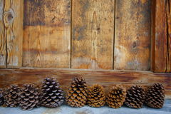 Pine cones and wood. In front of a chalet Stock Photos