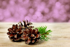 Pine cones on a wooden board against christmas bokeh Royalty Free Stock Photo