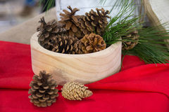 Pine cones in a wooden bowl Stock Images