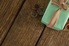 Pine cones and wrapped gift box on wooden table Royalty Free Stock Images