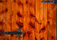 Pine Door Aspect. A wooden door made out of pine planks caught my eye, and particularly so due to the wrought iron lock and hinges. Certainly not and old door Royalty Free Stock Images