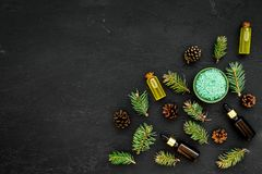 Pine essential oil in bottles on dark background top view copy space. Pattern with pine branch and cone.  Stock Images