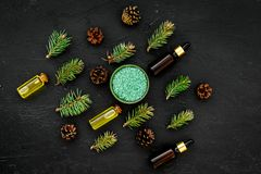 Pine essential oil in bottles on dark background top view copy space. Pattern with pine branch and cone.  Royalty Free Stock Photography