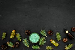 Pine essential oil in bottles on dark background top view copy space. Pattern with pine branch and cone.  Stock Photo