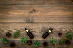 Pine essential oil in bottles on wooden background top view copy space. Pattern with pine branch and cone.  Royalty Free Stock Photography