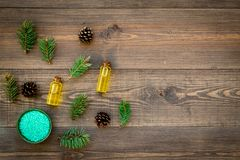 Pine essential oil in bottles on wooden background top view copy space. Pattern with pine branch and cone.  Stock Photo