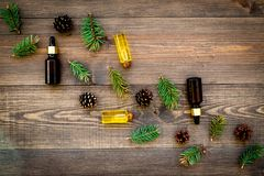 Pine essential oil in bottles on wooden background top view copy space. Pattern with pine branch and cone.  Stock Image