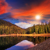Pine forest and lake near the mountain at sunset Stock Photos