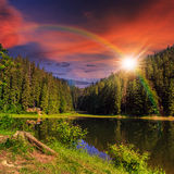 Pine forest and lake near mountain at sunset Stock Photo