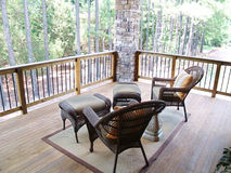 Pine Forest Overlook. Wicker furniture sitting on a wooden deck overlooking a pine tree forest Stock Photography