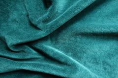 Pine green napped fabric in soft folds. Pine green velvet fabric in soft folds Royalty Free Stock Image