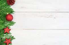 The Pine leaf with red star and christmas ball decoration on a w. The Pine leaf with red star and christmas ball decoration on white wooden board with copy space Royalty Free Stock Image