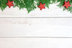 The Pine leaf with red star and christmas ball decoration on a w. Pine leaf with red star and christmas ball decoration on a white wooden board with copy space Stock Photo