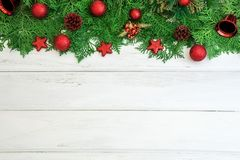 Pine leaf with red star and christmas ball decoration on white. The Pine leaf with red star and christmas ball decoration on white wooden board with copy space Stock Photo
