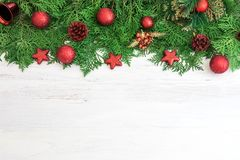 Pine leaf with red star and christmas ball decoration on white. The  Pine leaf with red star and christmas ball decoration on white wooden board with copy space Royalty Free Stock Photos