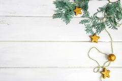 The Pine leaf with yellow gold star and christmas ball decoratio. Pine leaf with yellow gold star and christmas ball decoration on white wooden board with copy Royalty Free Stock Images